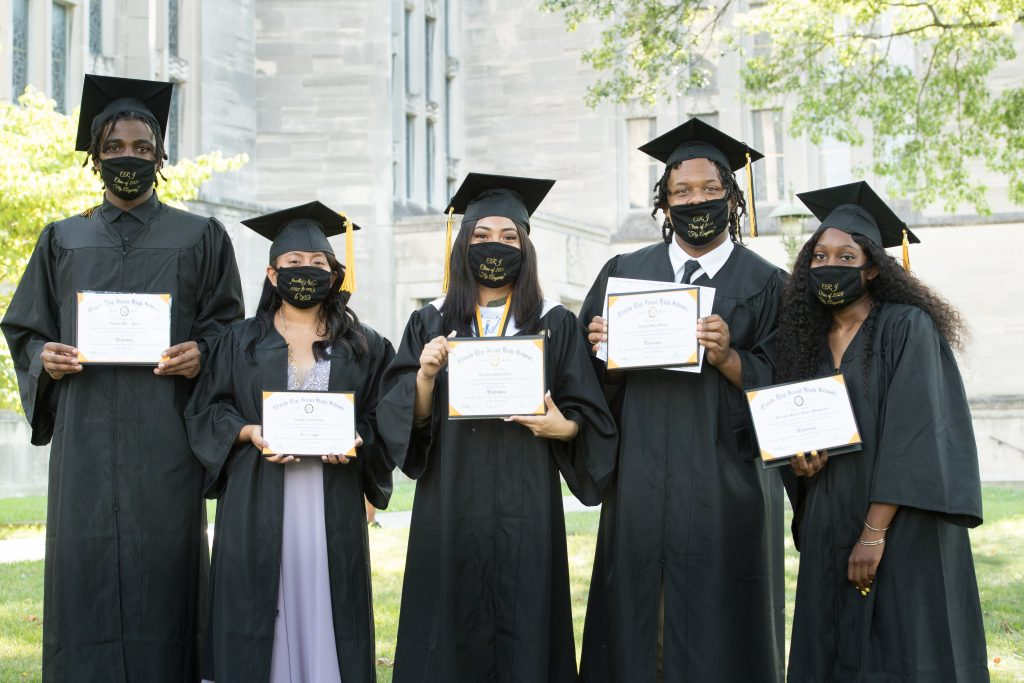 Five Cristo Rey Jesuit graduates pose with their diplomas and graduation-themed masks.
